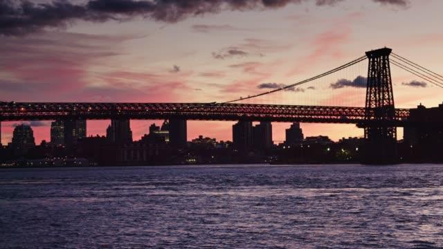 vídeos de stock, filmes e b-roll de ponte de williamsburg travessia ferroviária ao pôr do sol - williamsburg new york