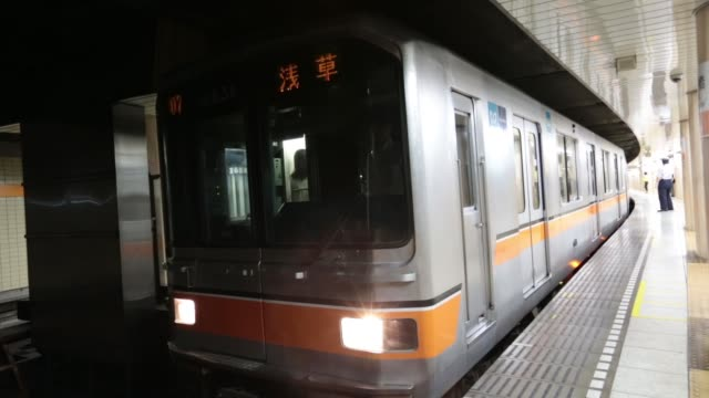 train departs a subway station in tokyo, japan, on thursday sept. 11 passengers board a crowded train at a subway station, a train arrives at a... - 地下鉄電車点の映像素材/bロール