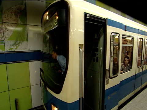 train driver checks passengers are safely on board doors close and u-bahn tube train departs station munich - u bahnsteig stock-videos und b-roll-filmmaterial