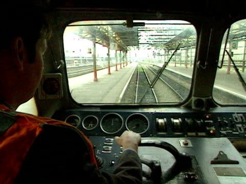 vidéos et rushes de a train driver moves train slowly along beside station platform 2000 - levier de contrôle