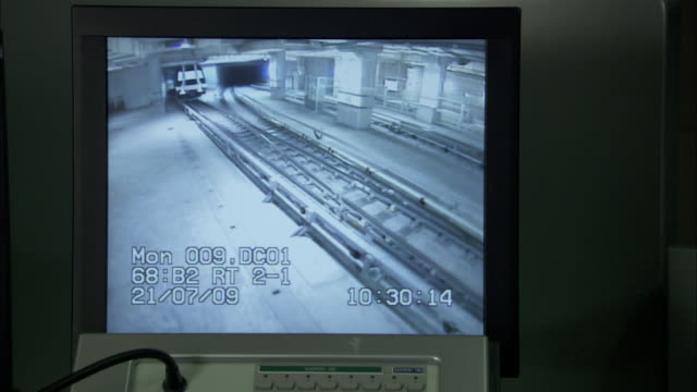 A train emerges from a tunnel on a closed circuit display.