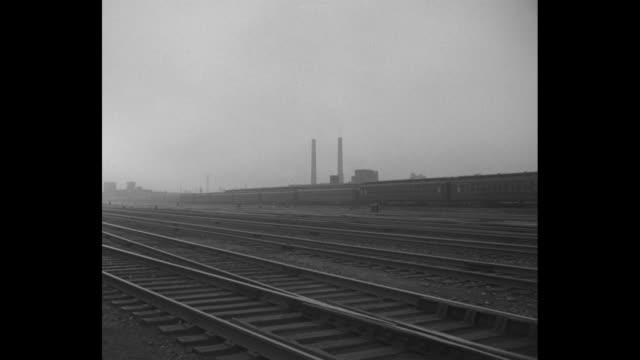 Train engine / LS passenger train moving / railroad tracks and empty passenger cars / CU train wheels slowly moving / engine driver inspecting train...