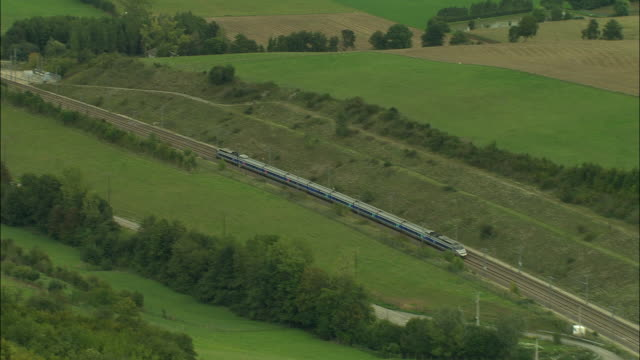 AERIAL WS TGV train exiting tunnel from behind trees and traveling across viaduct / Isere, France