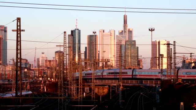 train goes in front of the skyline to the main station frankfurt am main at sunset - ケーブル線点の映像素材/bロール
