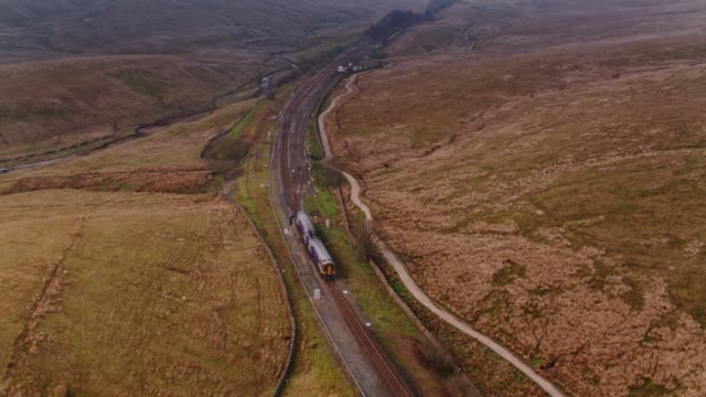 train heading north after crossing ribblehead viaduct - drone shot - rail transportation stock videos & royalty-free footage