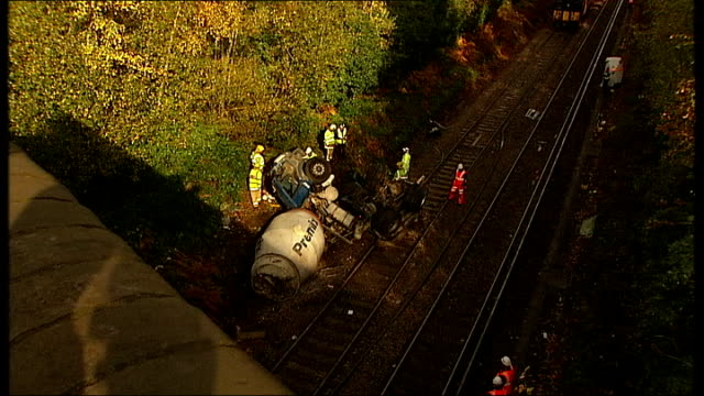 train hit by cement truck: emergency services at scene; england: surrey: oxshott: ext / evening emergency service workers towards hole in bridge wall... - surrounding wall stock-videos und b-roll-filmmaterial