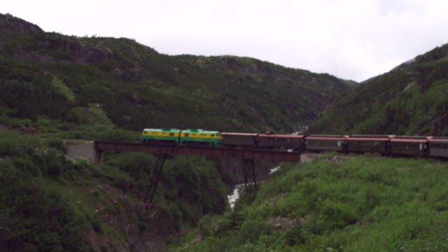 vídeos de stock, filmes e b-roll de train in alaska goes over bridge over rocky gorge - skagway
