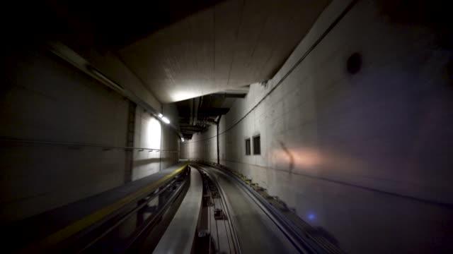 4k-zug im tunnel mit bewegungsunschärfe am flughafen - train vehicle stock-videos und b-roll-filmmaterial