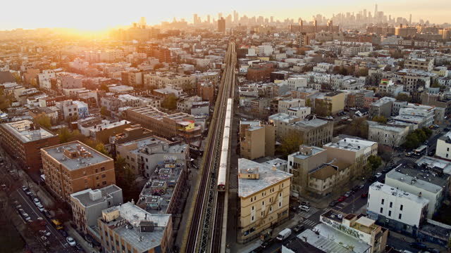 a train is riding across the residential district in brooklyn, new york, on the sunset. drone video with the forward and tilting-up accelerated camera motion. - brooklyn new york stock videos & royalty-free footage