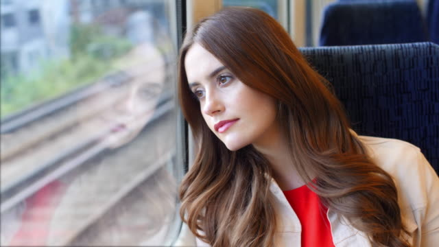 train journey. beautiful young woman looking out of the window. - brown hair stock videos & royalty-free footage