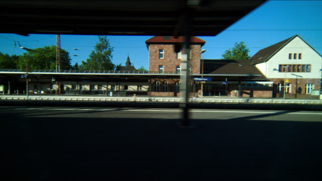 train leaves station with shadowy platform and railway tracks, parked rail carriages, blue sky, Dillingen, Saarland, Germany