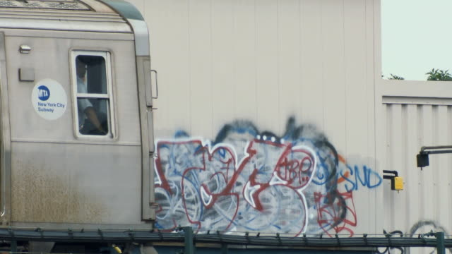 ms train leaving station in astoria queens, graffiti on wall behind / new york city, usa - hochbahn passagierzug stock-videos und b-roll-filmmaterial
