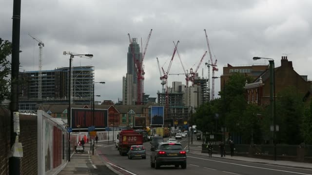 train lines run past battersea power station in london uk on friday may 2 cranes stand beside new skyscrapers during the construction of residential... - バタシー発電所点の映像素材/bロール
