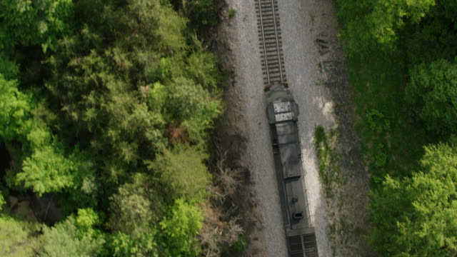 ws zo ts aerial pov train locomotive crossing creek and passing through forest area / north carolina, united states - schienenverkehr stock-videos und b-roll-filmmaterial