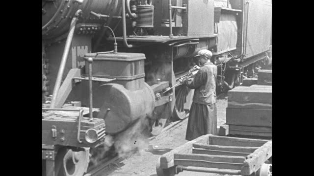 Train locomotive pulling in and stopping / woman climbing down from locomotive with cleaning can with spout in her hand and then cleaning part of...