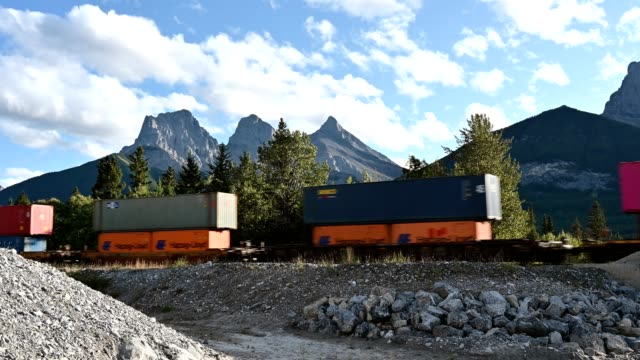train long freight transport on railway passing in three sisters mountains at canmore - british columbia stock videos & royalty-free footage