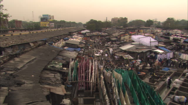 a train moves past a laundry operation in a mumbai neighborhood. - slum stock videos & royalty-free footage
