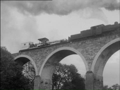 ws train moves slowly across viaduct with aerial work platform mounted on back of it and men are lowered down on platform to inspect viaduct / united kingdom - nur männer über 40 stock-videos und b-roll-filmmaterial