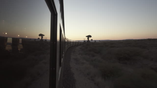 stockvideo's en b-roll-footage met train moving by landscape against clear sky, beautiful railroad journey during sunset - swakopmund, namibia - passenger train