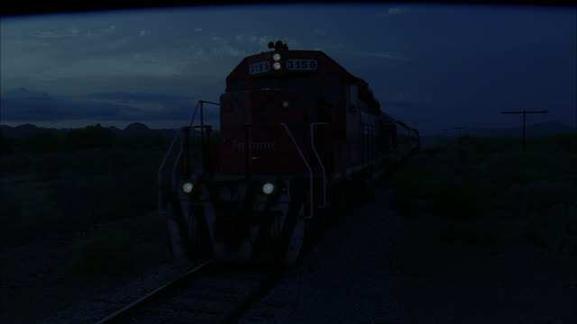 PAN Train moving down the tracks as darkness falls