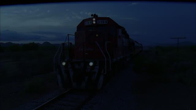 pan train moving down the tracks as darkness falls - lokomotive stock-videos und b-roll-filmmaterial