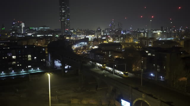 train moving in city centre at night aerial view. - manchester england stock videos & royalty-free footage