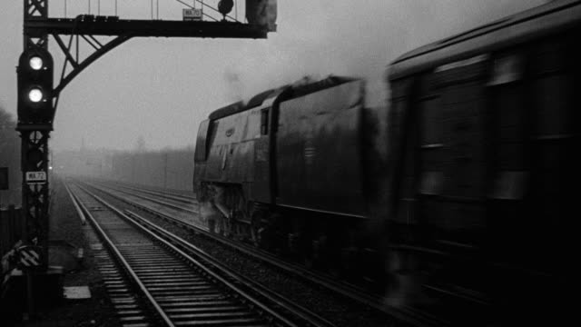 montage train moving on railroad across the landscape as day breaks / united kingdom - 1952 stock videos & royalty-free footage