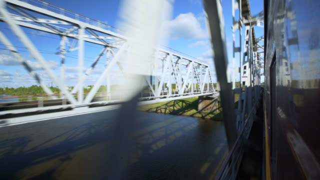 train moving on railway bridge over river against sky - novosibirsk, russia - brücke stock-videos und b-roll-filmmaterial