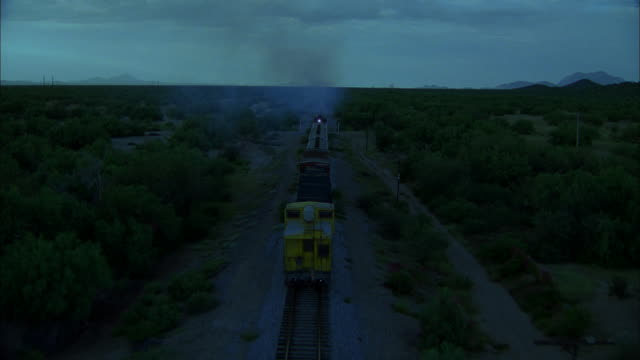AERIAL Train moving on tracks through scrub desert and drawing away with night falling