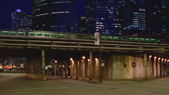 vidéos et rushes de ms el train moving over bridge at night with buildings in background / chicago, illinois - métro de chicago