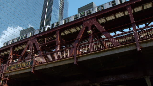 MS POV Train moving over Lake Street Bridge, modern buildings with reflection in background / Chicago, Illinois, United States