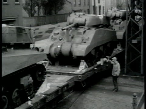 vídeos de stock, filmes e b-roll de train moving pulling flatbed cargo of light tanks out of rail yard soldier riding 'shotgun' on bulldozer on flatbed vs us army equipment moving on... - 1943