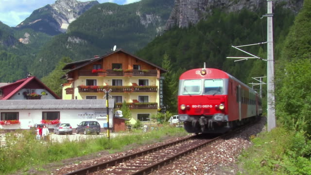 ws train moving through town at foot of mountains/ hallstatt, austria  - 2006 stock videos & royalty-free footage