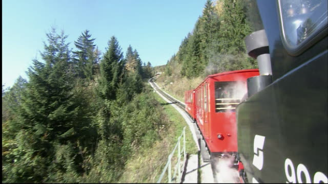 train of schafberg mountain railway ascending through woods, cut to trees and wolfgangsee below, st wolfgang, austria - オーストリア点の映像素材/bロール