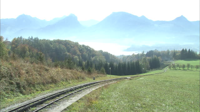 train of schafberg mountain railway ascends mountainside, forest and wolfgangsee in background, st wolfgang, austria - オーストリア点の映像素材/bロール