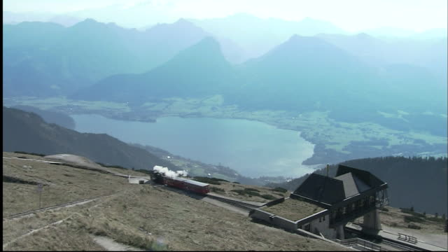 train of schafberg mountain railway departs from station to make its descent, wolfgangsee in background, st wolfgang, austria - オーストリア点の映像素材/bロール