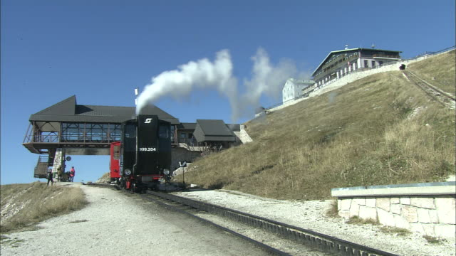 train of schafberg mountain railway departs from station to make descent, st wolfgang, austria - オーストリア点の映像素材/bロール