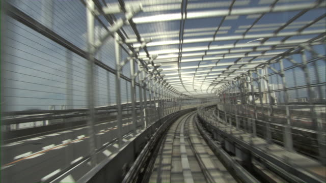 vidéos et rushes de pov train on elevated monorail track passing through modern glazed tunnel / tokyo, tokyo prefecture, japan - monorail