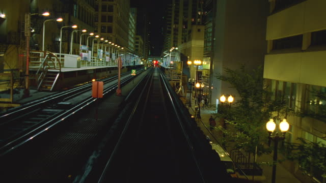 train pov on elevated tracks in downtown district at night / chicago, illinois - chicago elevated stock-videos und b-roll-filmmaterial