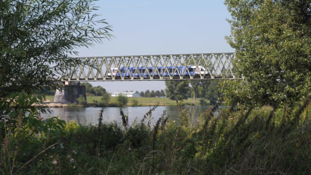 stockvideo's en b-roll-footage met train on the bridge over the maas at mook in limburg (netherlands) - kees van den burg