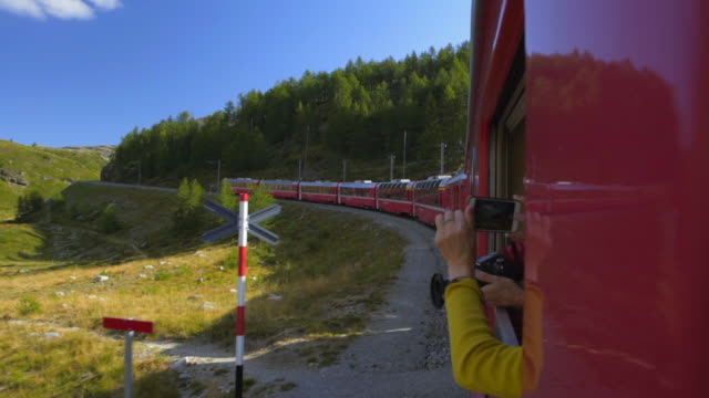 train passengers take photos of forests and rolling hills from side of red train in bernina pass - swiss alps, switzerland - mountain pass stock videos & royalty-free footage
