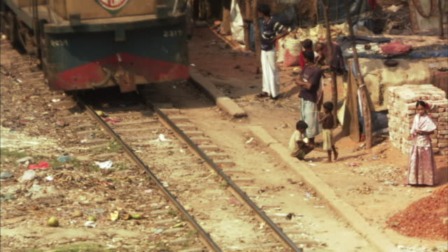 ha, ms, train passing by children and men standing near huts in shanty town, dhaka, bangladesh - bangladesh stock videos & royalty-free footage