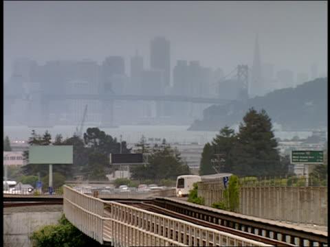 vídeos y material grabado en eventos de stock de bart train passing  city in background  san francisco  california  usa - bart
