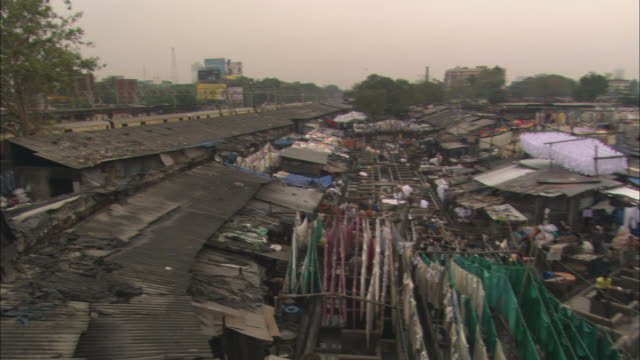 ha, pan, ws, train passing next to public outdoor laundry, mumbai, maharashtra, india - slum stock-videos und b-roll-filmmaterial