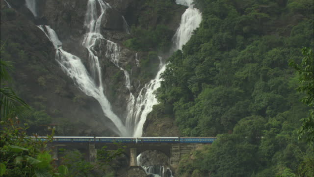 ws train passing over arch bridge in front of tall, rocky waterfall/ india - arch bridge stock videos & royalty-free footage
