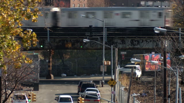 Train passing overhead on a grungy overpass near Boston avenue and vyse avenue in the bronx with cars driving underneath during the day