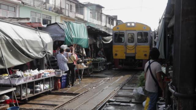 ws pov train passing through  middle of busy market / bangkok, thailand - bangkok stock videos & royalty-free footage