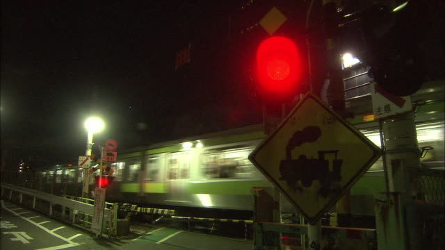 train passing through the railway crossing on the yamanote line at night; the crossing is the only left crossing among the yamanote line - level crossing stock videos & royalty-free footage