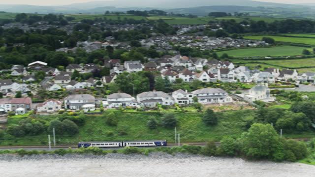 vídeos y material grabado en eventos de stock de tren pasando por debajo del puente de la carretera y la velocidad a lo largo de la costa cerca de morecambe, inglaterra - lancashire