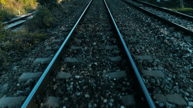 train point of view drone flying low over railroad train railroad track - ferrovia video stock e b–roll